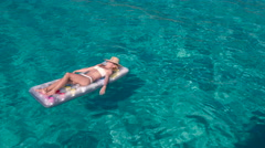 Smiling woman with a sun hat lying and tanning on air bed floatie Stock Footage