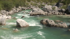 AERIAL, CLOSE UP: Amazing emerald maintain river running between big rocks Stock Footage