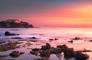 Castiglioncello old building on the rocks and sea on sunset. Tuscany, Italy. Stock Photos
