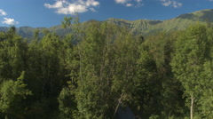 AERIAL: Flying above gravel road in wild forest with rocky mountains in distance Stock Footage