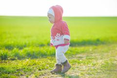 Happy little girl walking in the meadow and looking at sun Stock Photos