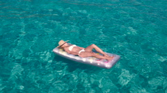 Young caucasian woman sun bathing on air mattress in crystal clear waters Stock Footage