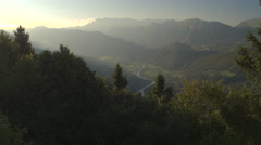 AERIAL: Meandering river winding through mountain valley in misty morning Stock Footage