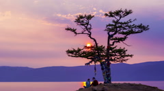 Beautiful sunset on lake Baikal, tree of desire, couple and tourists, timelapse Stock Footage