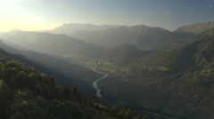 AERIAL: Mountain river running through beautiful green valley in misty evening Stock Footage