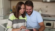 Young couple in kitchen looking at tablet pc. Man standing by his girlfriend Stock Footage