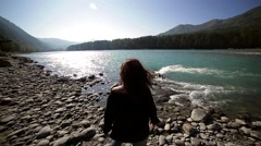 Young woman spread her arms on the shore of the turquoise mountain river Stock Footage