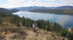 Drone Flying Past Hiker on Mountain Top Above Lake Roosevelt, Washington Stock Footage