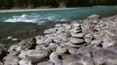 Cairn, Stones on the shore of the turquoise mountain river Stock Footage