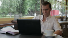 A man looks at the laptop and bursts out laughing, while sitting in a summer Stock Footage