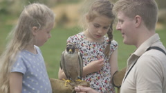 4K Children at falconry centre listening to handler talk about peregrine falcon Stock Footage