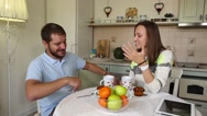 Young couple talking while having meal in kitchen at home. Conversation between Stock Footage