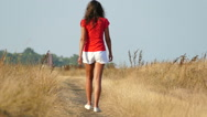 Slow motion. Woman in red  go  on  dirt road Stock Footage