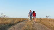 Slow motion. Adult  couple go  on  dirt road . Stock Footage