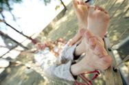 Feet of woman and man relaxing in hammock Stock Photos