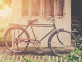 Vintage bicycle or old bicycle vintage park on old wall home. Stock Photos