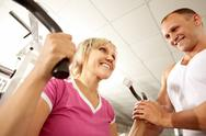 Trainer helping woman with exercises in gym Stock Photos