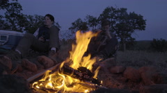 Men Sit Around Campfire, One Whittles A Stick, The Otherd Talk, Camera Tilts Up Stock Footage