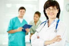 Portrait of beautiful female doctor looking at camera with her colleagues behind Stock Photos