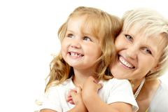 Happy grandmother embracing her granddaughter and looking at camera Stock Photos