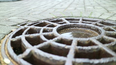 Cover the drain hatch on the road. Small ripples on the surface of the puddle. Stock Footage