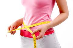 Woman measuring her waist after diet Stock Photos