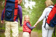 Little girl looking at camera with her parents walking outdoors Stock Photos