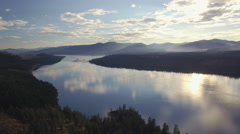 Epic Cinemtaic Aerial Reveal of Scattered Clouds Over Lake with Mountain Stock Footage