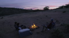 Group Of Hunters Sit Around Campfire And Talk Stock Footage