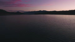 Low Aerial Pan Up to Pink Sunset on Lake Perfect for Movie Intro Stock Footage