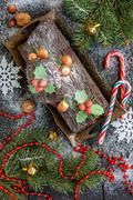 Cake Christmas log, candy, tree branches and a garland. Stock Photos