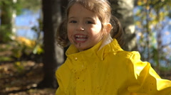 Little funny girl with a dirty face is jumping in a dirty puddle. Slow motion. Stock Footage