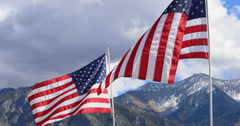 US American flags against high mountain peaks DCI 4K Stock Footage