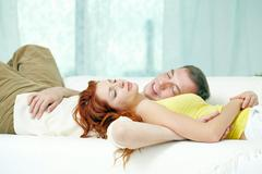 Young couple sleeping together on sofa Stock Photos