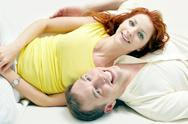 Happy couple lying on bed together and looking at camera Stock Photos