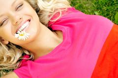 Young woman lying on grass and holding chamomile in her mouth Stock Photos