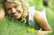 Smiling young woman lying on grass and looking at camera Stock Photos