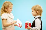 Two children standing and exchanging presents, gift for girl and post card for b Stock Photos