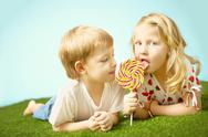 Two cute children lying on grass and eating lollipop together Stock Photos