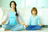 Mother with daughter meditating together at home Stock Photos