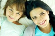 Smiling mother and her daughter lying in bed and looking at camera Stock Photos