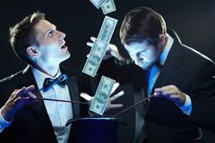 Two magicians making money with their wands in top hat Stock Photos