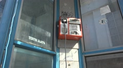 Vandalized rusty payphone booth Hanging handset 4k UHD.Tilt down . Stock Footage