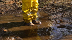 Little girl in a yellow rubber suit is jumping in a puddle.  Slow Motion Stock Footage
