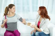 Young woman declining a cake offered by her friend Stock Photos