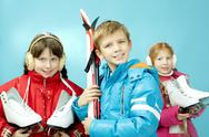 Portrait of little girls with skates and a boy with skis isolated on blue Stock Photos