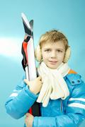 Portrait of a little boy in warm sports clothing and with skis isolated on blue Stock Photos