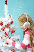 Little girl in warm clothing decorating a Christmas tree in snow Stock Photos