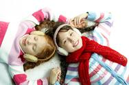 Two little girls in warm clothing lying on snow holding hands Stock Photos