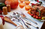 Close-up of silverware on thanksgiving table with roasted chicken Stock Photos